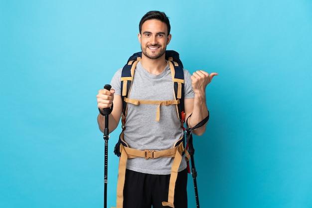 Jonge blanke man met rugzak en wandelstokken geïsoleerd op blauwe achtergrond naar de zijkant om een product te presenteren