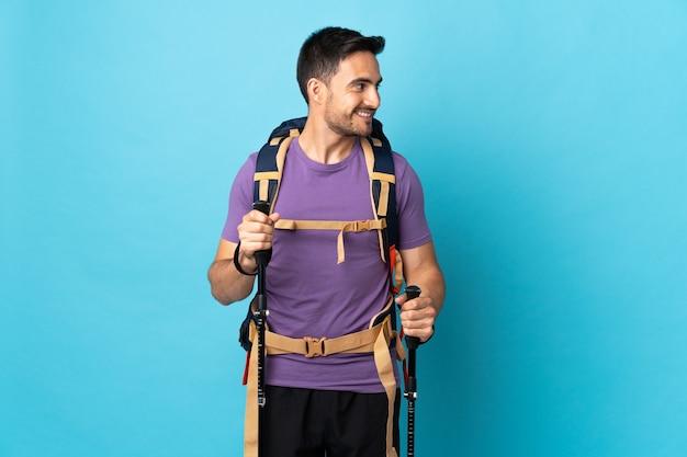 Jonge blanke man met rugzak en wandelstokken geïsoleerd op blauwe achtergrond op zoek kant