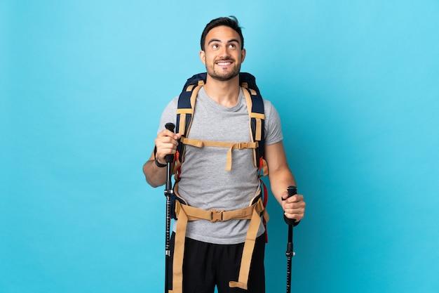 Jonge blanke man met rugzak en wandelstokken geïsoleerd op blauwe achtergrond opzoeken tijdens het glimlachen