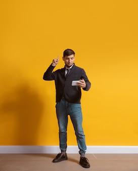 Jonge blanke man met smartphone full body lengte portret geïsoleerd over gele muur