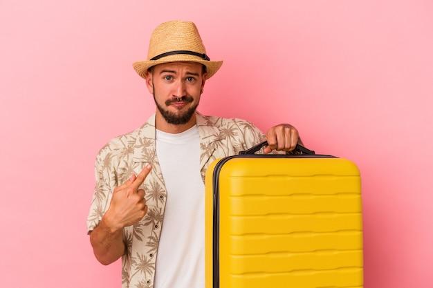 Jonge blanke man met tatoeages die geïsoleerd op een roze achtergrond gaat reizen en met de vinger naar je wijst alsof uitnodigend dichterbij komt.