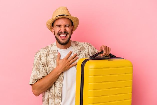 Jonge blanke man met tatoeages die geïsoleerd op roze achtergrond gaat reizen, lacht hardop terwijl hij de hand op de borst houdt.