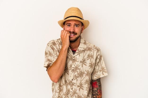 Jonge blanke man met tatoeages die zomerkleren dragen die op witte achtergrond worden geïsoleerd en vingernagels bijten, nerveus en erg angstig.