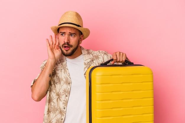 Jonge blanke man met tatoeages gaat reizen geïsoleerd op een roze achtergrond en probeert een roddel te luisteren.