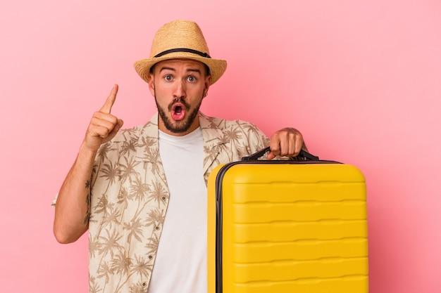 Jonge blanke man met tatoeages gaat reizen geïsoleerd op roze achtergrond met een idee, inspiratie concept.