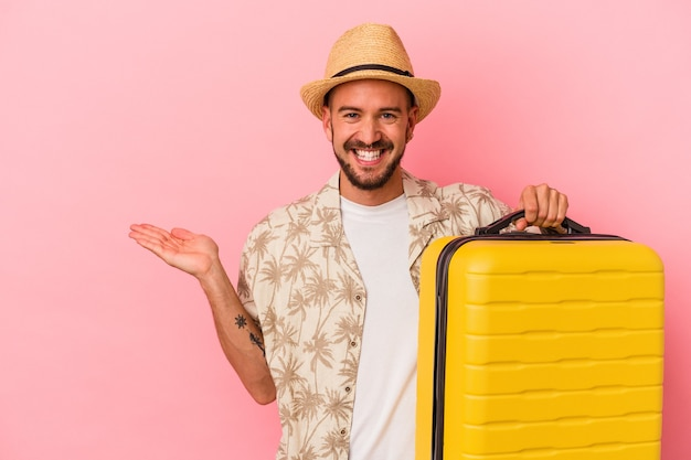 Jonge blanke man met tatoeages gaat reizen geïsoleerd op roze achtergrond met een kopie ruimte op een palm en met een andere hand op de taille.