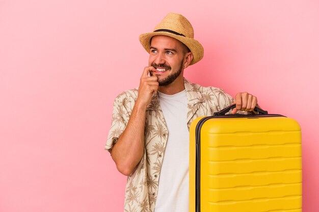 Jonge blanke man met tatoeages gaat reizen geïsoleerd op roze achtergrond ontspannen denken aan iets dat naar een kopieerruimte kijkt.