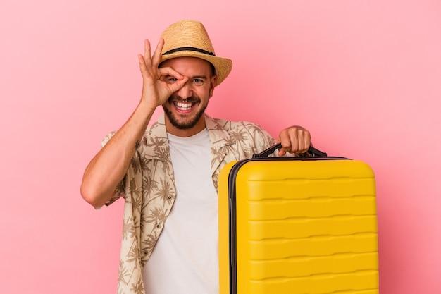 Jonge blanke man met tatoeages gaat reizen geïsoleerd op roze achtergrond opgewonden houden ok gebaar in de gaten.