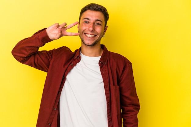 Jonge blanke man met tatoeages geïsoleerd op gele achtergrond dansen en plezier maken.