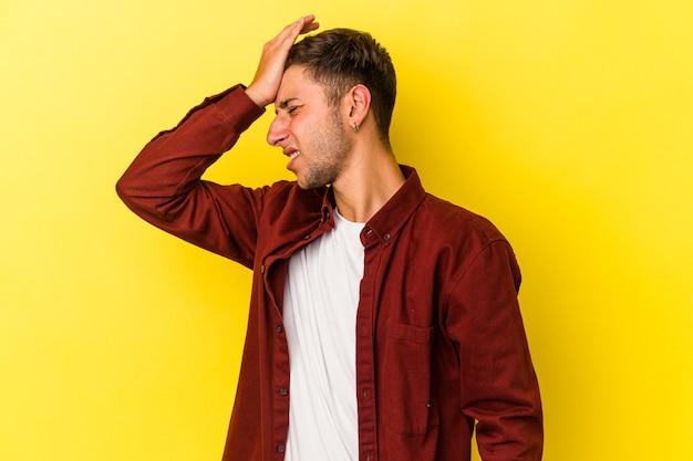 Jonge blanke man met tatoeages geïsoleerd op gele achtergrond iets vergeten, voorhoofd slaan met palm en ogen sluiten.