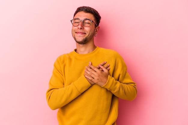 Jonge blanke man met tatoeages geïsoleerd op gele achtergrond lachen houden handen op het hart, concept van geluk.