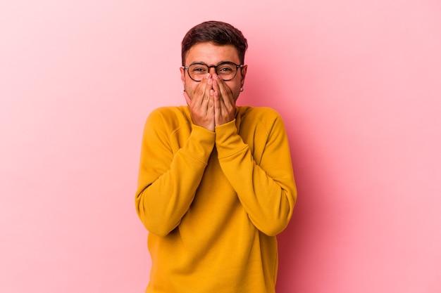 Jonge blanke man met tatoeages geïsoleerd op gele achtergrond lachen om iets, mond bedekken met handen.
