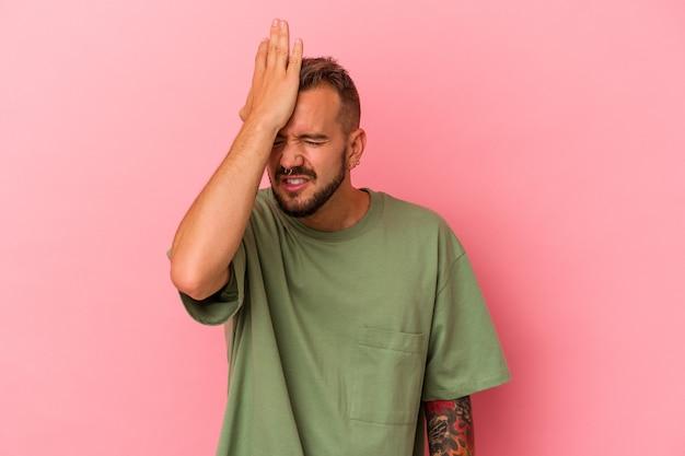 Jonge blanke man met tatoeages geïsoleerd op roze achtergrond iets vergeten, voorhoofd met palm slaan en ogen sluiten.