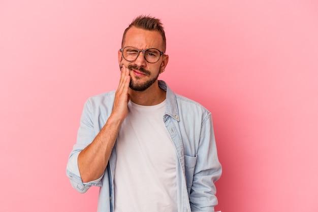 Jonge blanke man met tatoeages geïsoleerd op roze achtergrond met een sterke tandenpijn, kiespijn.