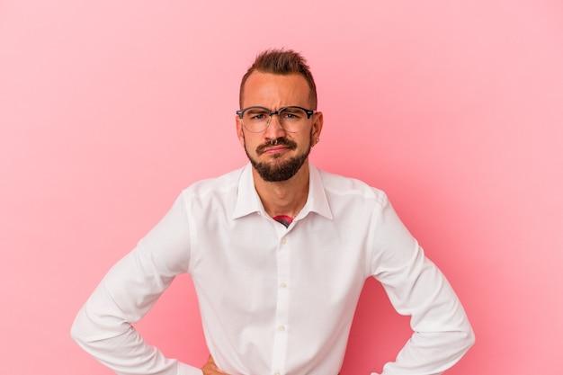 Jonge blanke man met tatoeages geïsoleerd op roze achtergrond verdrietig, serieus gezicht, ellendig en ontevreden voelen.
