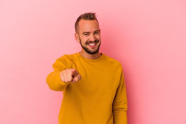Jonge blanke man met tatoeages geïsoleerd op roze achtergrond vrolijke glimlach wijzend naar voren.