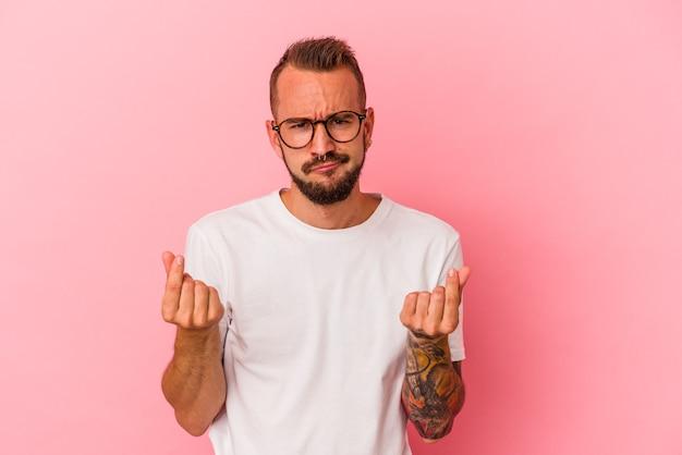 Jonge blanke man met tatoeages geïsoleerd op roze achtergrond waaruit blijkt dat ze geen geld heeft.