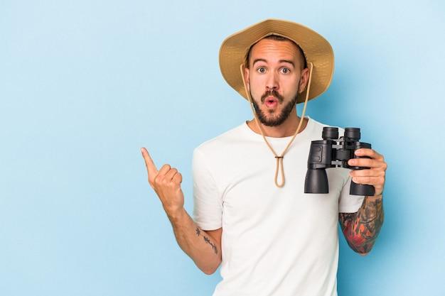 Jonge blanke man met tatoeages met een verrekijker geïsoleerd op een blauwe achtergrond die naar de zijkant wijst