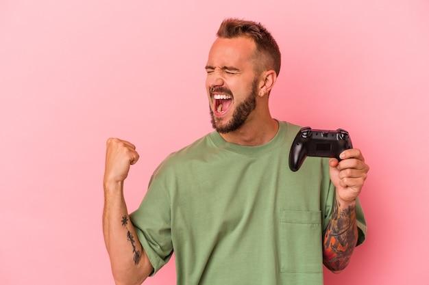 Jonge blanke man met tatoeages met spelbesturing geïsoleerd op roze achtergrond die vuist opheft na een overwinning, winnaar concept.