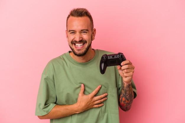 Jonge blanke man met tatoeages met spelbesturing geïsoleerd op roze achtergrond lachen en plezier hebben.