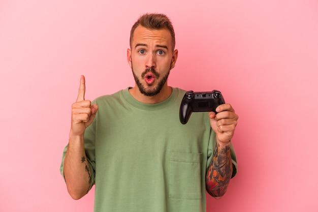 Jonge blanke man met tatoeages met spelbesturing geïsoleerd op roze achtergrond met een geweldig idee, concept van creativiteit.