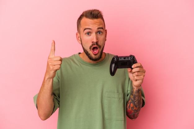Jonge blanke man met tatoeages met spelbesturing geïsoleerd op roze achtergrond met een idee, inspiratie concept.