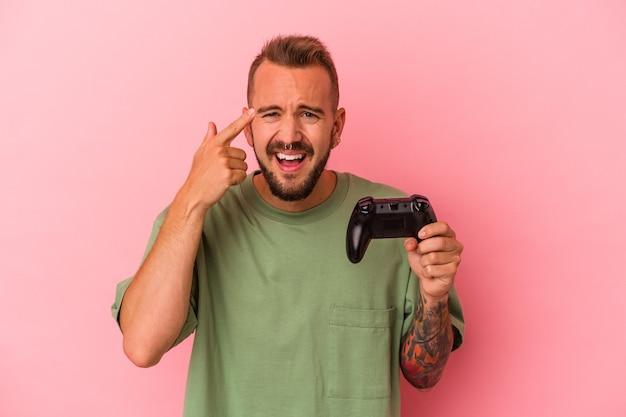 Jonge blanke man met tatoeages met spelbesturing geïsoleerd op roze achtergrond met een teleurstelling gebaar met wijsvinger.