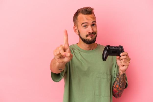 Jonge blanke man met tatoeages met spelbesturing geïsoleerd op roze achtergrond met nummer één met vinger.