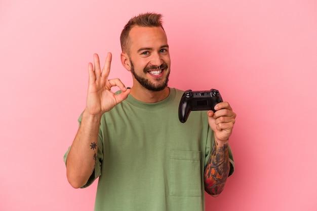 Jonge blanke man met tatoeages met spelbesturing geïsoleerd op roze achtergrond vrolijk en zelfverzekerd weergegeven: ok gebaar.