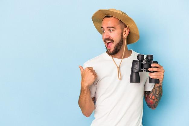 Jonge blanke man met tatoeages met verrekijker geïsoleerd op blauwe achtergrond wijst met duimvinger weg, lachend en zorgeloos.