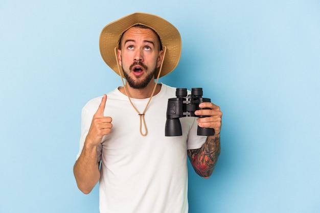 Jonge blanke man met tatoeages met verrekijker geïsoleerd op blauwe achtergrond wijzend ondersteboven met geopende mond.
