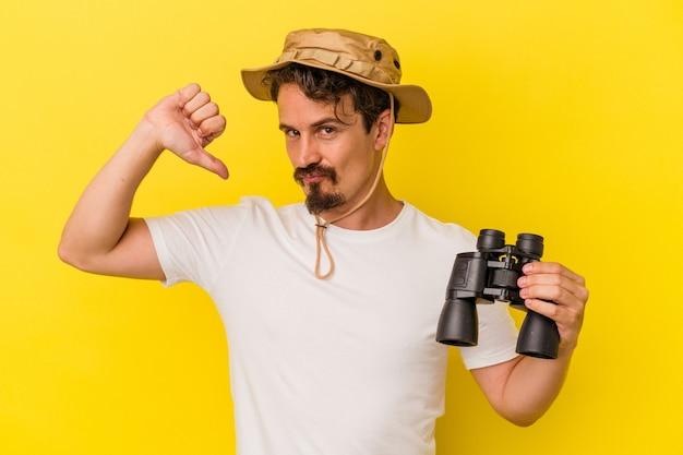Jonge blanke man met verrekijker geïsoleerd op gele achtergrond voelt zich trots en zelfverzekerd, voorbeeld om te volgen.