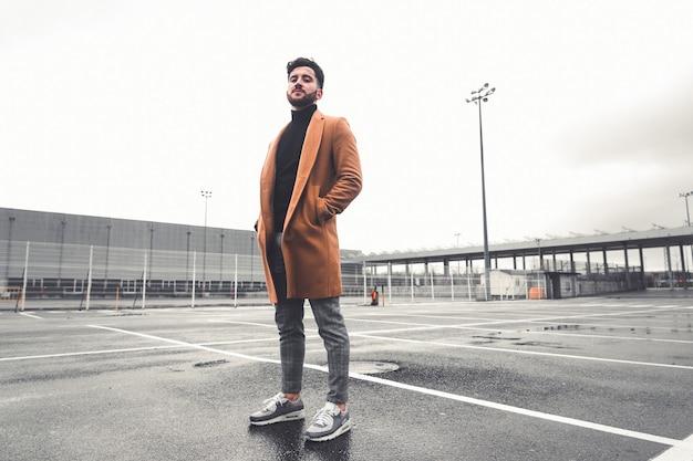 Jonge blanke man met vrijetijdskleding op een parkeerplaats