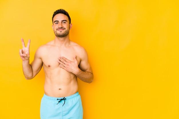 Jonge blanke man met zwembroek op gele muur een eed afleggen, hand op de borst zetten.
