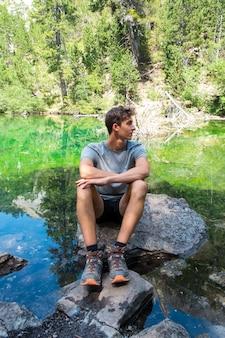 Jonge blanke man ontspannen van een meer tijdens een bergtrekking avontuurlijke reis tienerjongen