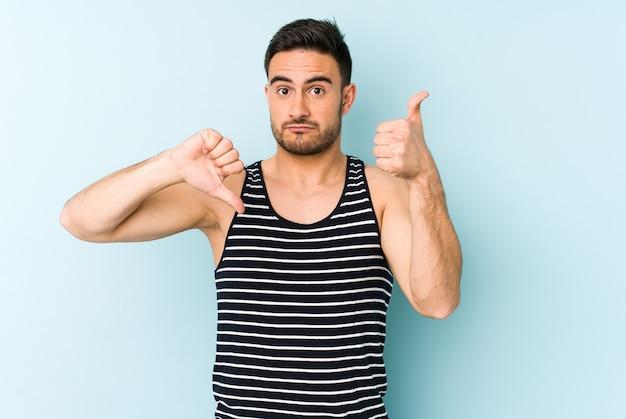 Jonge blanke man op blauw duimen opdagen en duimen naar beneden, moeilijk kies concept