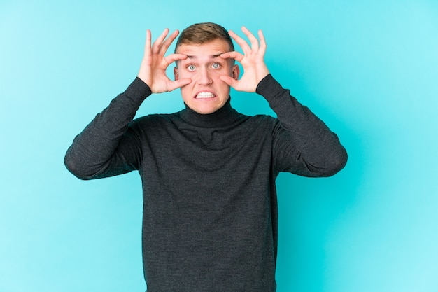Jonge blanke man op blauw met ogen geopend om een kans op succes te vinden.