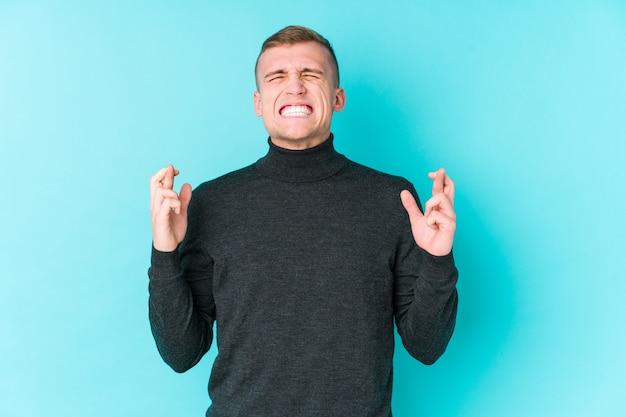 Jonge blanke man op blauwe kruising vingers voor geluk