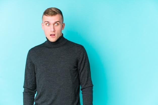Jonge blanke man op een blauwe muur wordt geschokt vanwege iets dat ze heeft gezien.