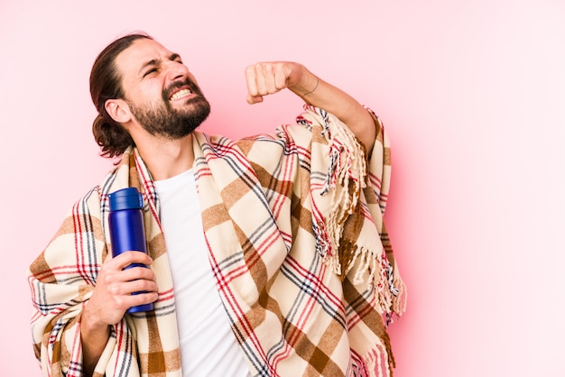 Jonge blanke man op een camping dag met een thermos fist na een overwinning te verhogen