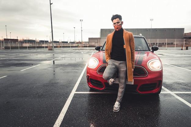 Jonge blanke man op een parkeerplaats met een rode auto erachter