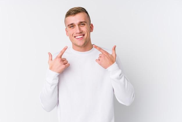 Jonge blanke man op een witte achtergrond glimlacht, wijzende vingers naar mond.
