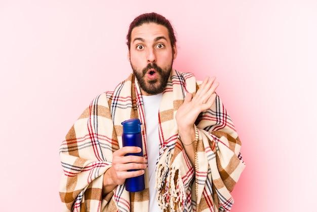 Jonge blanke man op kampeerdag met een thermosfles verrast en geschokt.
