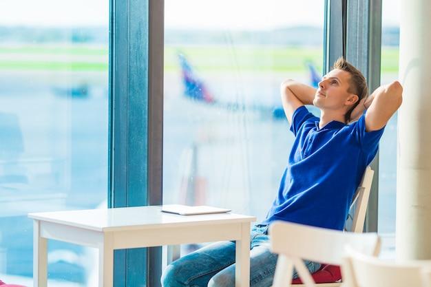 Jonge blanke man op luchthaven binnen wachten op instappen