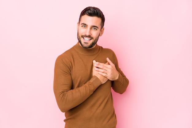 Jonge blanke man op roze geïsoleerd heeft vriendelijke uitdrukking, handpalm tegen borst te drukken. liefde concept.