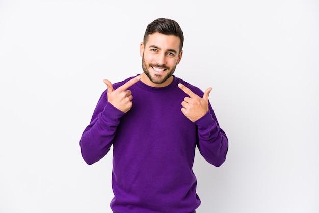 Jonge blanke man op wit geïsoleerde glimlach, wijzende vingers naar mond.