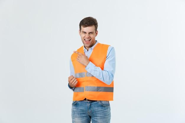 Jonge blanke man op witte achtergrond met aannemersuniform en veiligheidshelm verrast met een idee of vraag wijzende vinger met blij gezicht, nummer één.