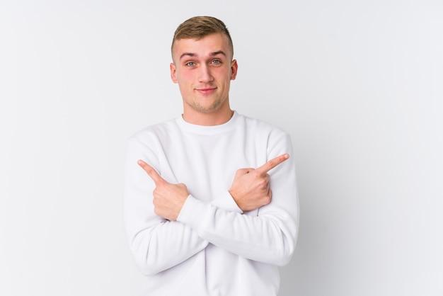 Jonge blanke man op witte muur wijst zijwaarts, probeert te kiezen tussen twee opties.