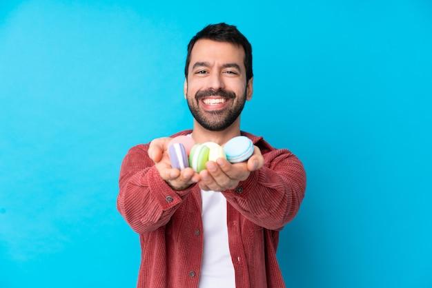 Jonge blanke man over geïsoleerde blauwe muur met kleurrijke franse macarons