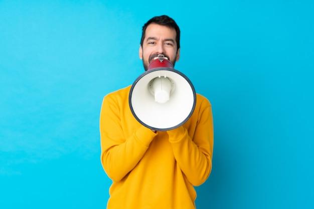 Jonge blanke man over geïsoleerde blauwe muur schreeuwen door een megafoon